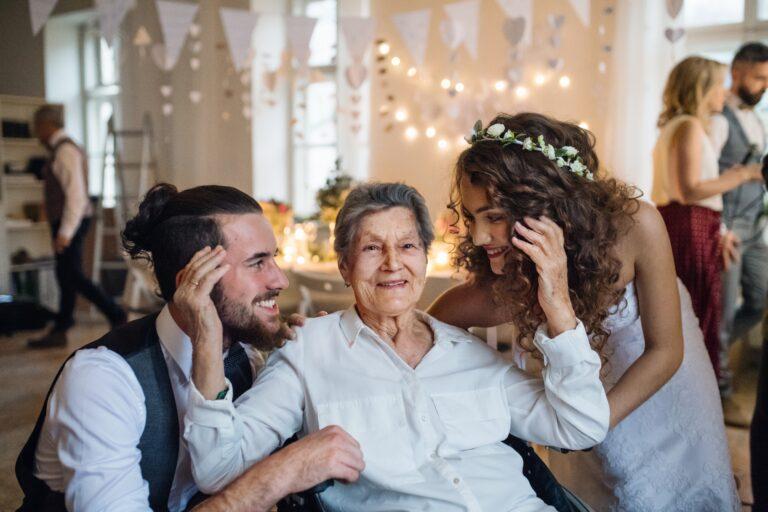 Un jeune couple avec grand-mère sur un mariage, posant pour une photo